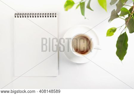 Mockup Top View Of An Open Blank Notebook On A Spiral, , White Porcelain Cup With Coffee And Leaves