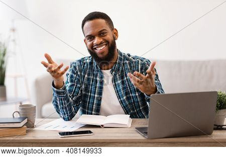 Positive African Business Guy Talking To Camera Sitting At Laptop In Modern Office. Professional Occ