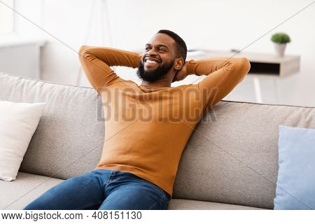 Happy African American Man Relaxing Sitting On Sofa Holding Hands Behind Head At Home. Comfort And C