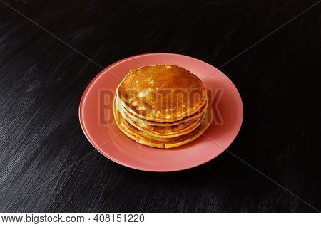Pile Of Pancakes On Pink Plate On Black Surface.