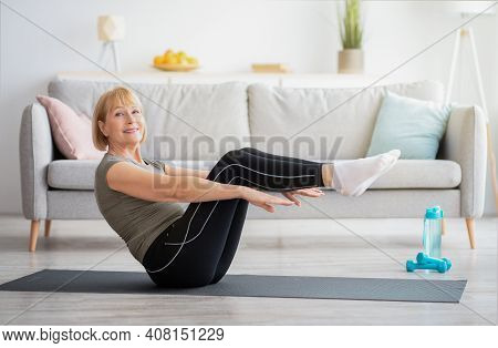 Happy Senior Woman Doing Abs Exercises On Yoga Mat At Home. Positive Mature Lady Working Out Her Cor