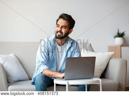 Portrait Of Pensive Arab Freelancer Guy Working With Laptop Computer At Home And Looking Aside, Thin
