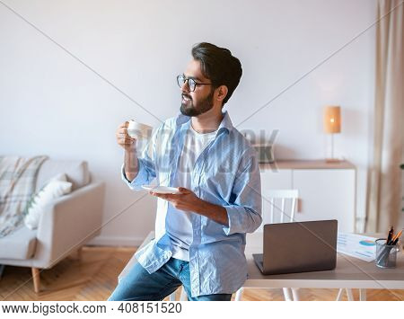 Handsome Eastern Man Relaxing With Cup Of Coffee After Working At Home Office, Smiling Millennial Ar