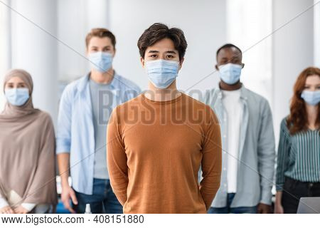 New Reality, Epidemic Concept. Portrait Of Asian Male Teen Wearing Protective Medical Mask Standing