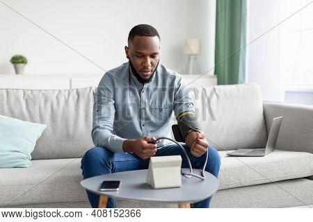 Hypertension. African Man Measuring Arterial Blood Pressure Having Health Problem Sitting On Sofa At