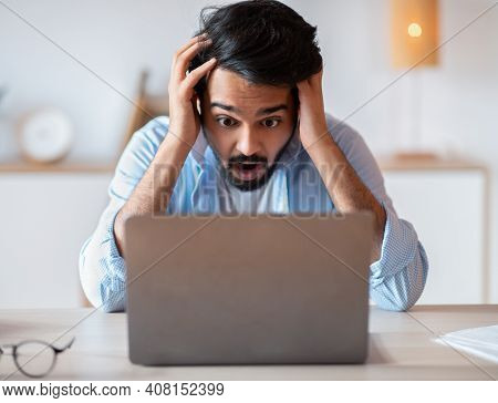 Deadline Stress. Frustrated Arab Man Looking At Laptop Screen And Touching Head In Shock, Eatern Fre