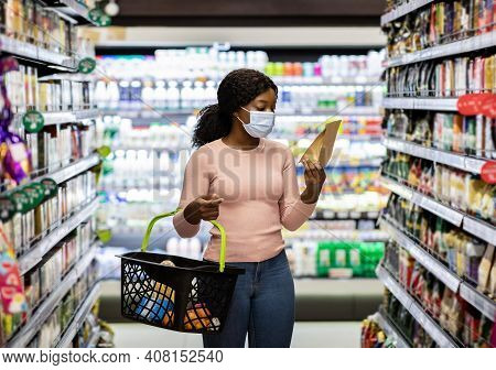 Young Black Woman In Face Mask Shopping For Groceries At Huge Supermarket. Millennial African Americ