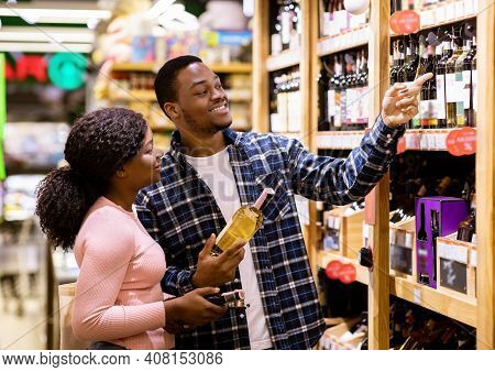 Happy Black Man And His Girlfriend Buying Wine At Liquor Department Of Supermarket. Lovely African A