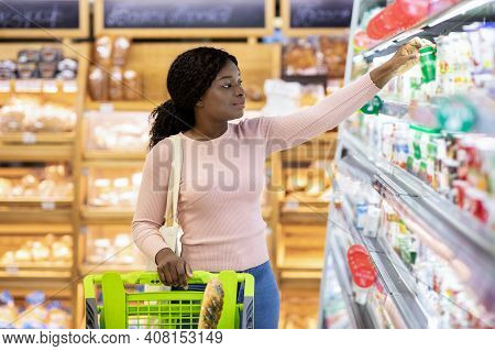 Beautiful Black Woman Buying Products At Dairy Department Of Huge Supermarket. Young African America