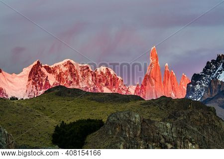 Picturesque mountain range, illuminated by the sunrise sun. Mountain peak in Patagonia. The grand crimson dawn over the mountain range Fitzroy. The concept of extreme, active and photo tourism