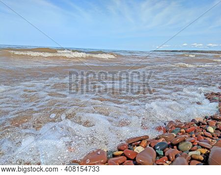 Waves Wash Up Brightly Colored Rocks Along The Shoreline Of Lake Superior At Porcupine Mountains Wil