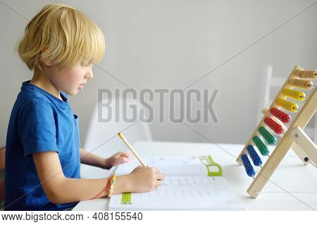 Elementary Student Boy Doing Homework At Home. Child Learning To Count, Solves Arithmetic Examples,