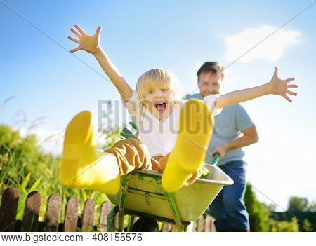 Happy Little Boy Having Fun In A Wheelbarrow Pushing By Dad In Domestic Garden On Warm Sunny Day. Ac