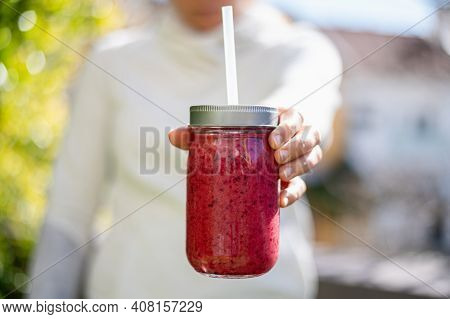 The Girl Holds A Berry Smoothie In A Glass Jar. Proper Nutrition. Orange, Red Berries And Banana Smo