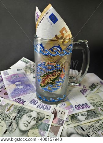 Various Banknotes Arranged Over A Dark Background On Which Is Built A Half-liter Glass Containing Eu