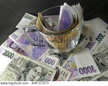 Various Banknotes Arranged Over A Dark Background On Which Is Placed A Glass In Which There Are Euro