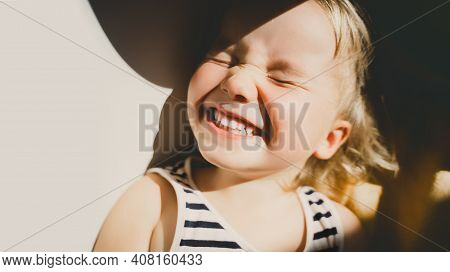 Cutest Little Girl Smiling And Squinting In Sunlight. Happy Toddler Having Fun. Portrait Of Playful