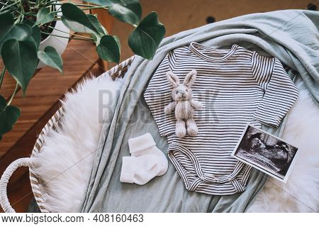 Baby Changing Basket With Ultrasound Image, Baby Bodysuit, Knitted Rabbit Toy. Still Life Of Child P