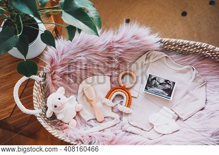 Baby Changing Basket With Ultrasound Image, Baby Bodysuit, Soft And Wooden Toys. Still Life Of Child