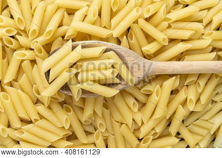 A Wooden Spoon Over A Lot Of Penne Macaroni Background Texture
