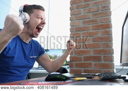 Male Gamer In Headphones Emotionally Reacts To Winning Game. Profession Gamer And Their Earnings Con