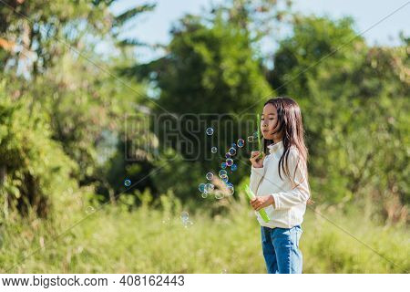 Happy Asian Little Cute Girl Child Having Fun And Enjoying Outdoor Play Blowing Soap Bubbles During