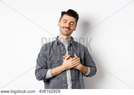 Romantic Happy Man Holding Hands On Heart And Smiling With Closed Eyes, Dreaming Of Something, Feeli