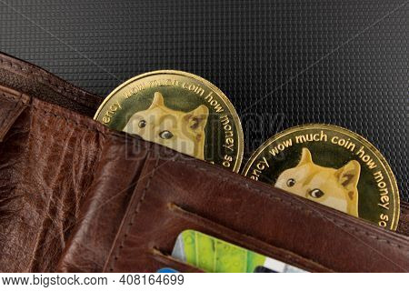 Dogecoins In A Wallet Over Laptop Surface
