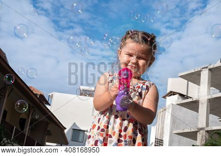 The Child Blows Bubbles. Girl Playing With Bubbles Gun
