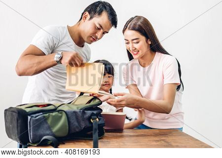 Happy Asian Family Father And Mother With Daughter Packing School Bag With Books Before Going To Sch