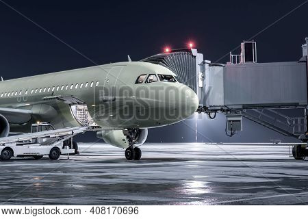 The Passenger Airplane Stands At The Jetway On An Airport Night Apron. The Baggage Compartment Of Th
