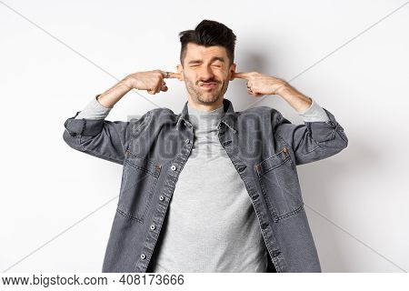 Annoyed Young Man Plug Ears With Fingers And Grimacing From Loud Noise, Disturbed By Noisy Neighbour