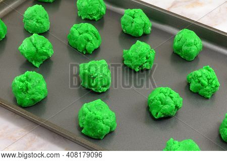 Balls Of Raw Green Saint Patrick's Day Cookie Batter Placed On Nonstick Baking Sheet