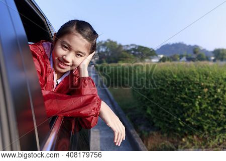 Asian Little Girl Looking Something Out The Car. In The Morning, The Girl Was Looking At Something O