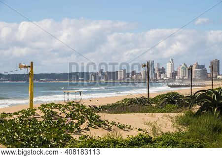 Dune Covered With Vegetation And Buildings In Background