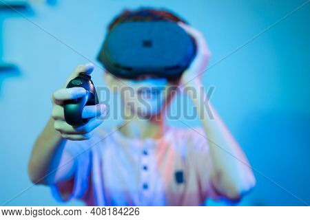 Selective Focus On Joystick, Young Kid Playing Video Game By Wearing Vr Or Virtual Reality Headset U