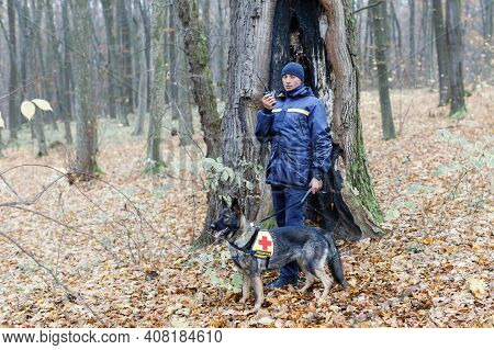 A Male Rescuer Holds A Dog On A Leash.