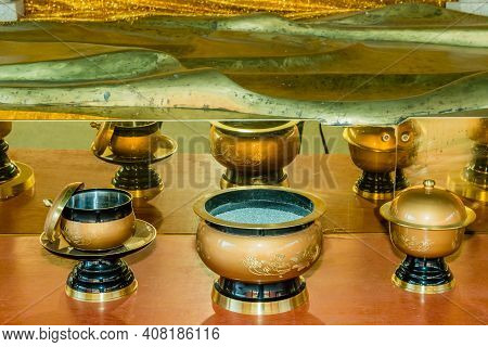 Ceremonial Incense Bowls In Front Of Mirror Under Reclining Buddha Statue At Manbolsa Temple In Yeon
