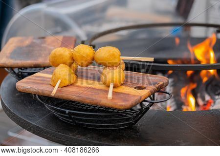 Crispy Yellow Potato Skewer On Wooden Cutting Board At Summer Outdoor Food Market: Close Up. Barbecu