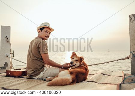 A Man And A Dog Pet Relax Near The Sea. Travel, Vocation, Holiday Concept.