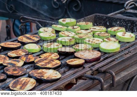 Close Up: Process Of Cooking Fresh Eggplant And Zucchini Slices On Grill Over Charcoals At Summer Lo