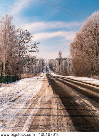 Winter Snowy Road Stretching Beyond The Blue Sky Horizon. Ice On The Highway. Vehicle Path. Road Mar