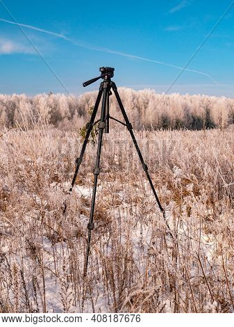 A Photographers Tripod Against The Backdrop Of A Winter Landscape. The Work Of A Photographer. Blue