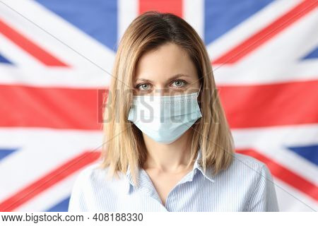Portrait Of Woman In Protective Mask Against Background Of British Flag. British Strain Of Coronavir