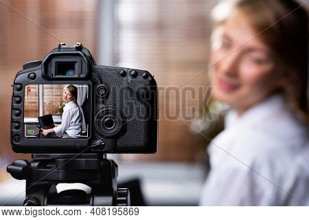 Young Female Blogger Looking At Camera And Talking A Video Recording Holding Laptop At Home. Social