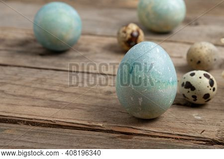 Colorfully Painted Easter Eggs On A Wooden Table.