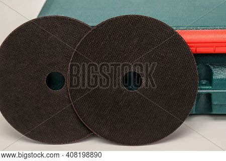 Abrasive Black Wheel, Grinding Wheel On The Background Of The Green Toolbox. Abrasive Materials, Dis