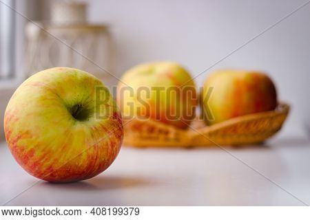 A Few Ripe Apples On A White Surface. Rear Background Is Blurred