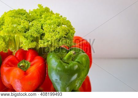 A Few Red And Green Bell Peppers Along With Salad Leaves
