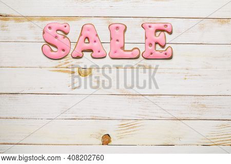 Sale Word Made From Pink Homemade Gingerbread Biscuit On White Wood Plank Tabletop. Copy Space.